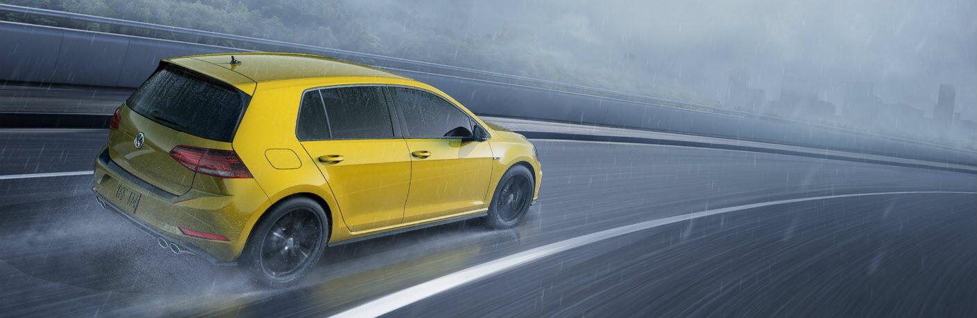 Exterior view of a gold 2019 Volkswagen Golf R driving around a race track in the rain