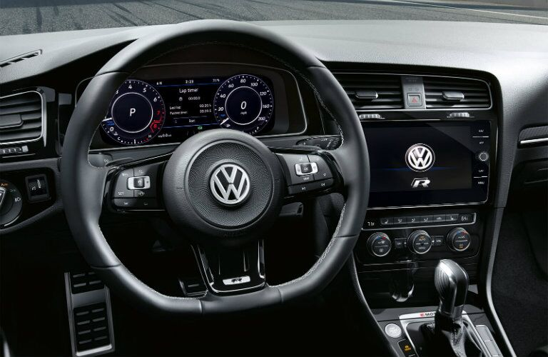 Interior view of a black steering wheel, Volkswagen Digital Cockpit, and touchscreen inside a 2019 Volkswagen Golf R