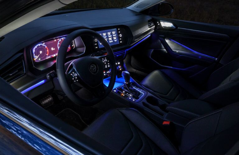 Interior view of a 2019 Volkswagen Jetta with blue ambient lighting and black seating