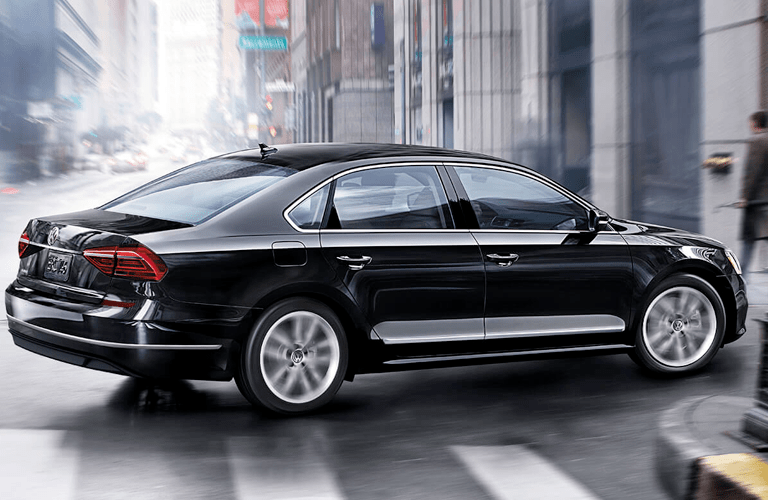 Exterior view of a black 2018 Volkswagen Passat turning down a side street in the city