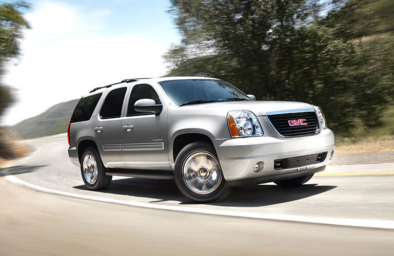 silver 2010 GMC Yukon driving down highway
