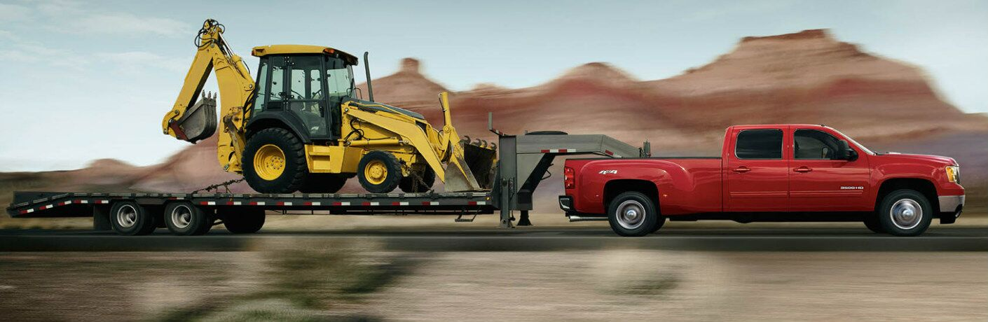 red 2013 GMC Sierra hauling construction equipment