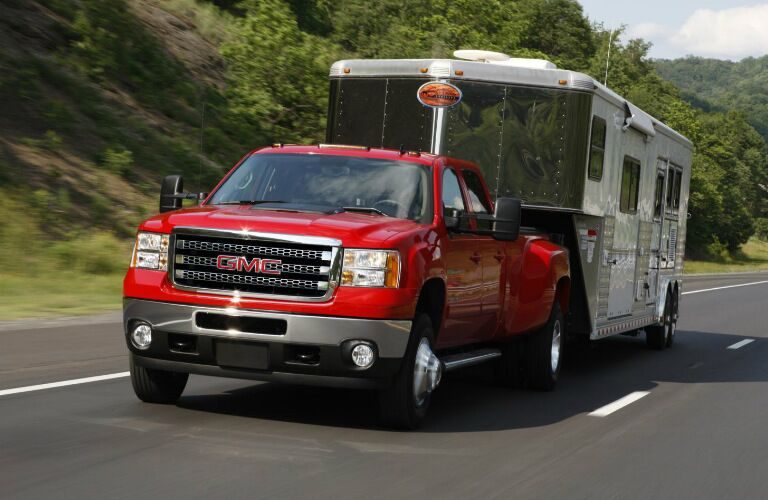 red 2013 GMC Sierra towing trailer behind it