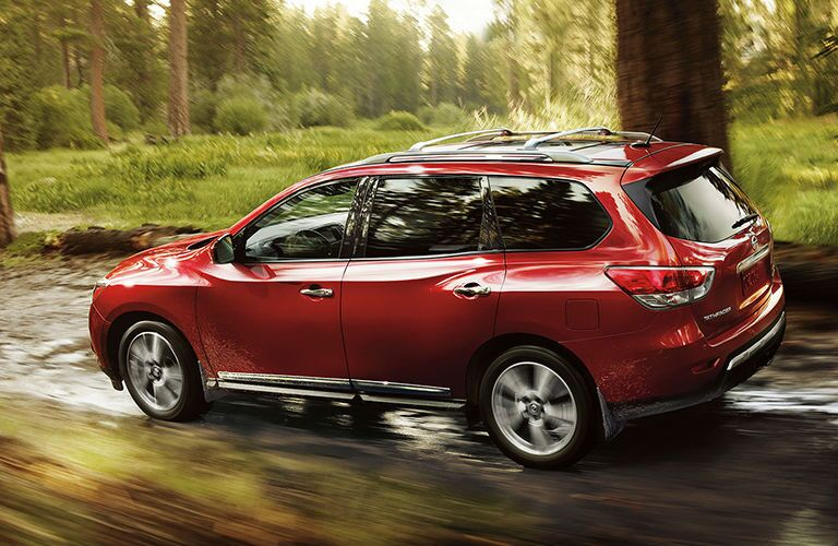 red 2013 Nissan Pathfinder driving through forest