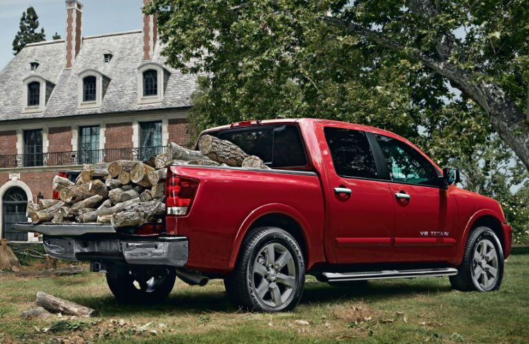 red 2013 Nissan Titan pickup truck hauling wood