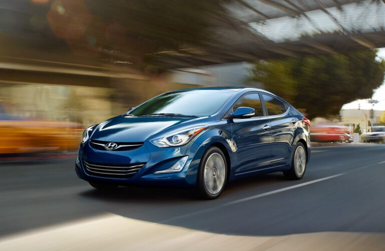 blue Hyundai Elantra driving down street from the front