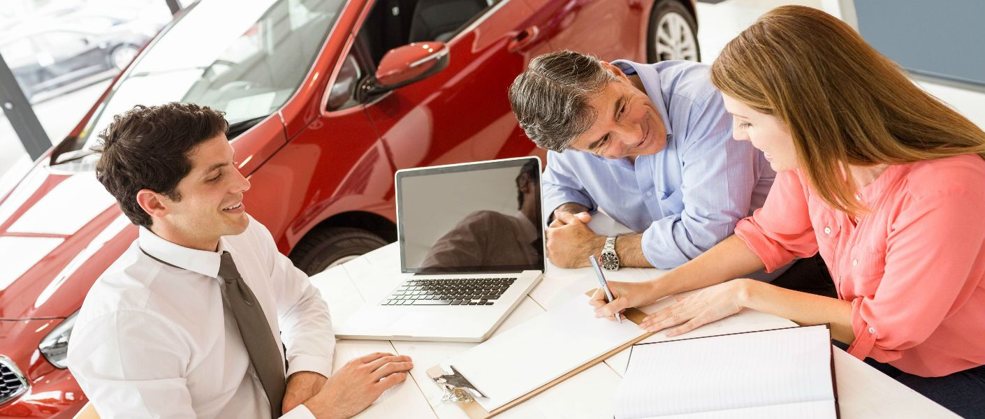 customers signing paperwork and buying car