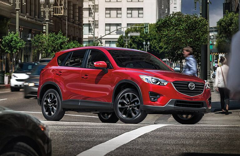 Red Mazda CX-5 turns a corner in a city.