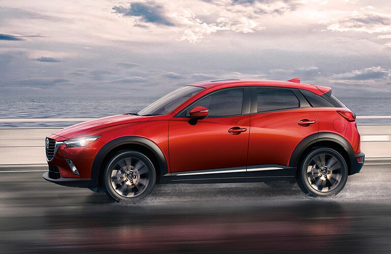 Red Mazda CX-3 drives along a road by a beach, spraying up a little water with its wheels.