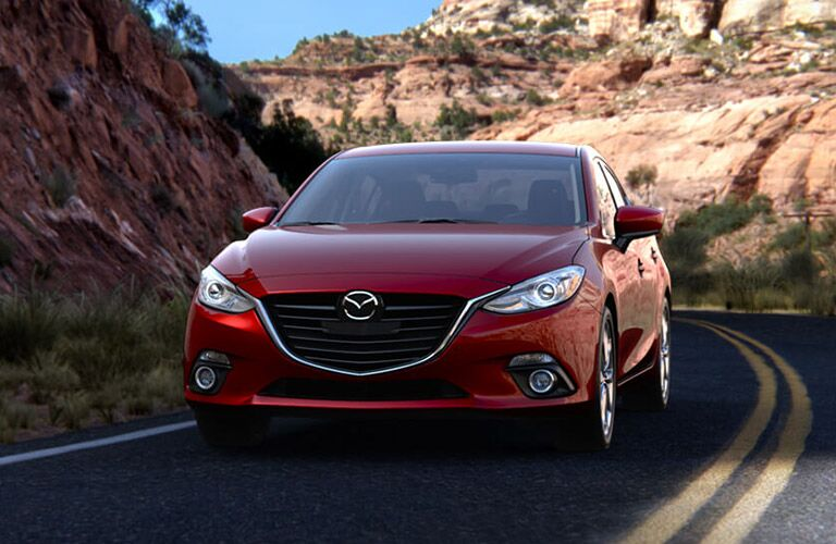 Red Mazda3 drives around a desert highway curve.