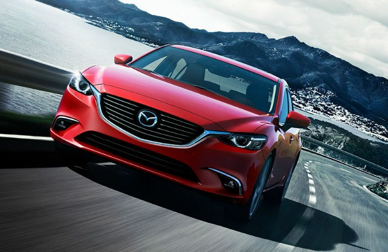 Red 2016 Mazda6 cruises down a highway away from a coastal city.