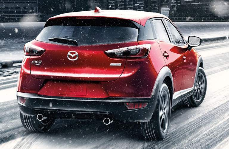 Red 2017 Mazda CX-3 drives over a snowy road. All-wheel drive could possibly help in this situation.