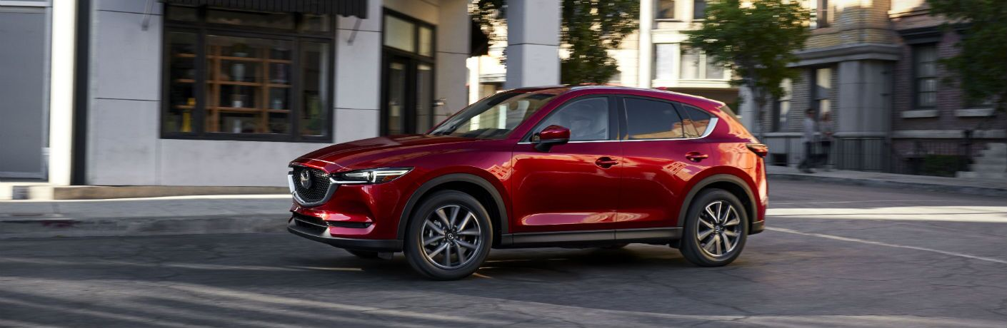 Red 2017 Mazda CX-5 drives through a city.