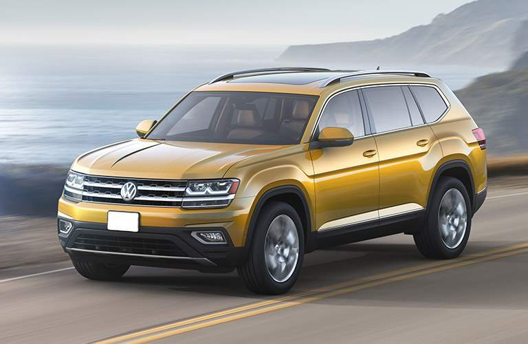 Yellow Volkswagen Atlas drives down a seaside highway on a cloudy day.