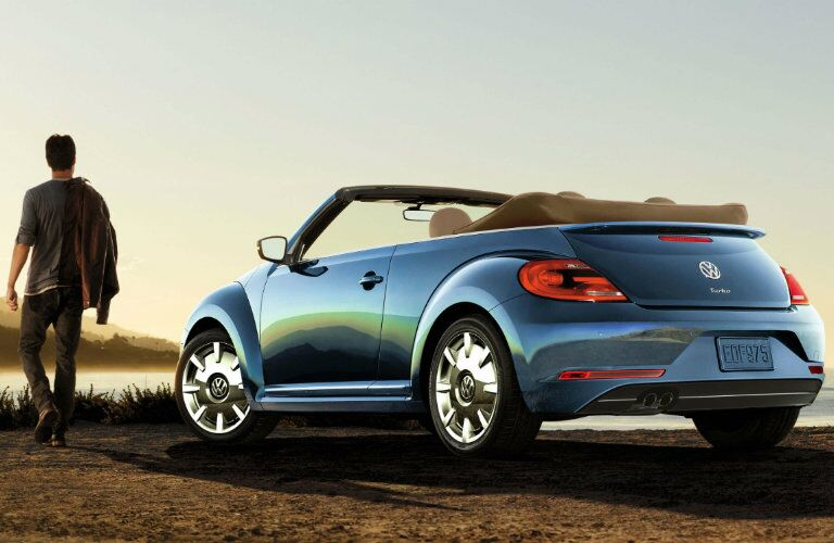 Blue 2017 Volkswagen Beetle convertible parked on a shoreline with a guy walking out.