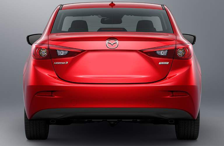 Rear view of red 2018 Mazda3 on gray background