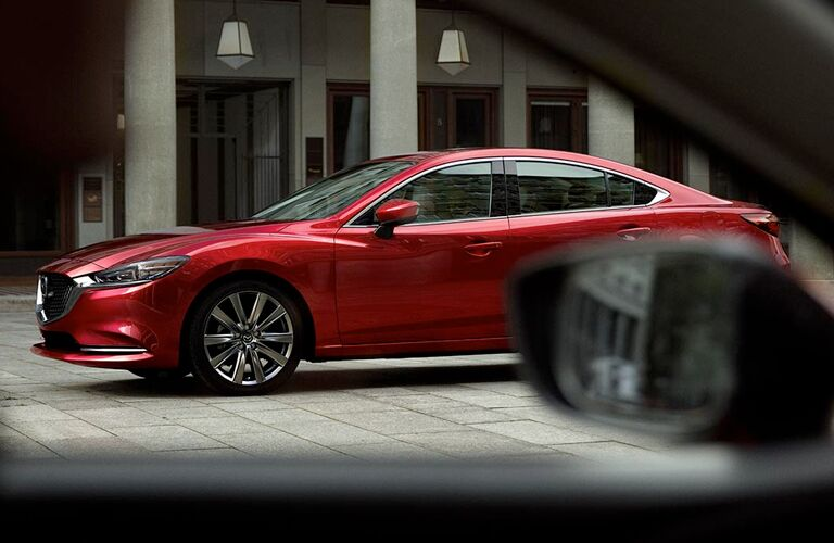 Profile view of red 2018 Mazda6 driving on tiled street