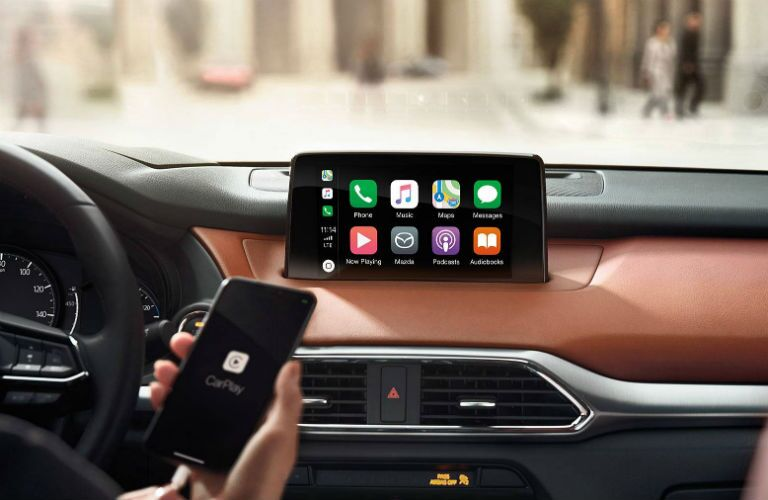 A hand holds a smartphone in front of the Apple CarPlay-equipped infotainment system inside the 2019 Mazda CX-9.