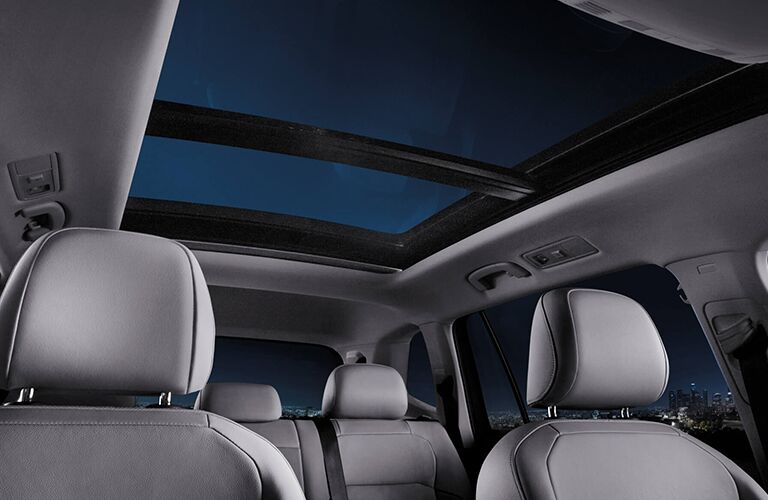 Interior view gazing up at the panoramic moonroof inside the 2019 Volkswagen Tiguan at night.