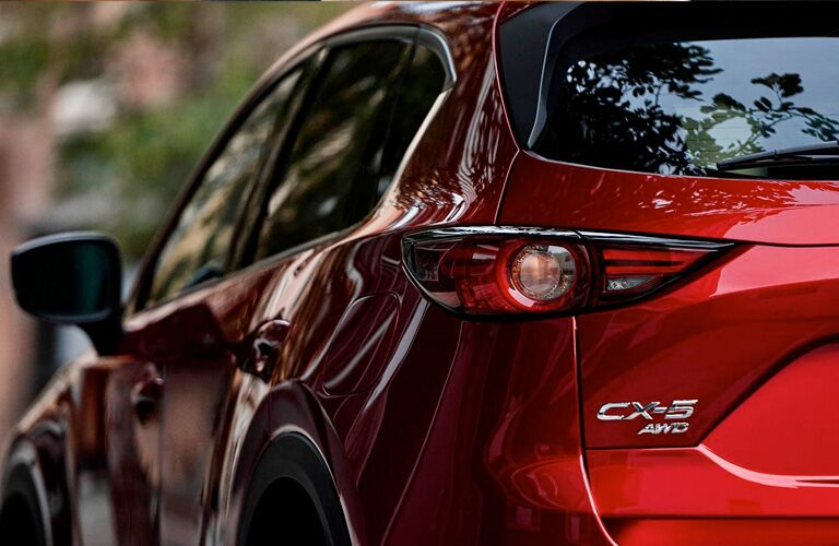 View of the left side and back left half of a red 2019 Mazda CX-5 with AWD.
