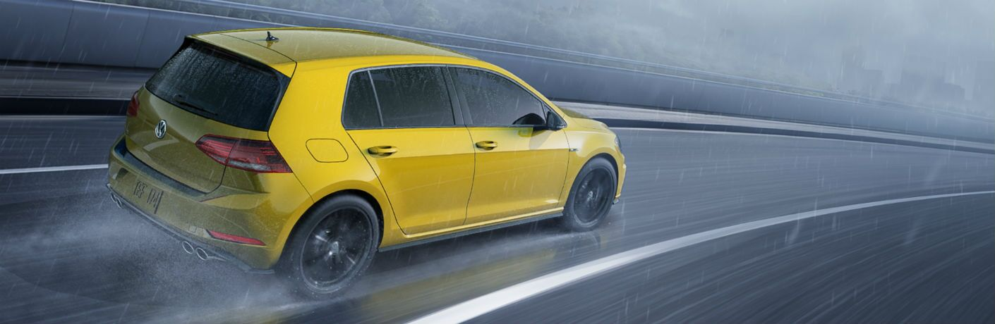 Rear passenger side exterior view of a yellow 2019 VW Golf R