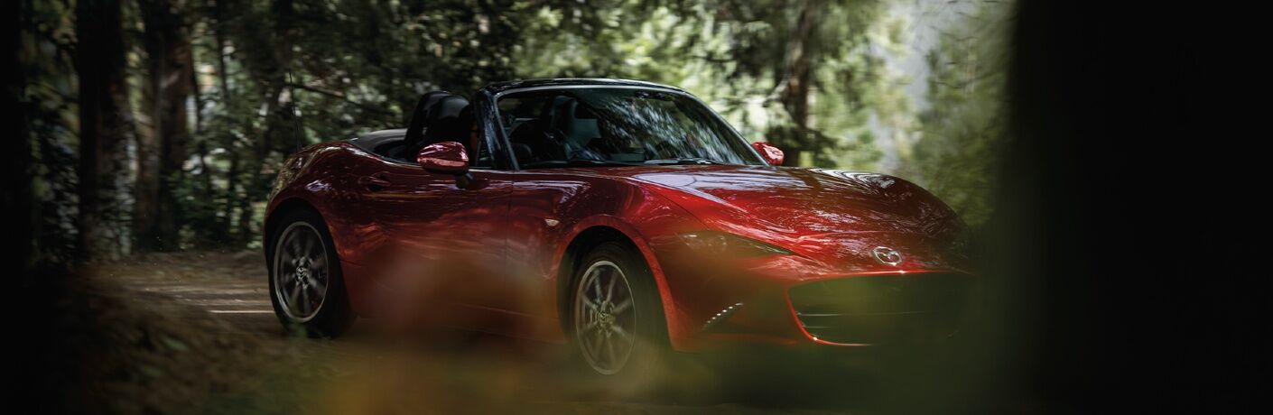 2020 Miata partially obscured by tree