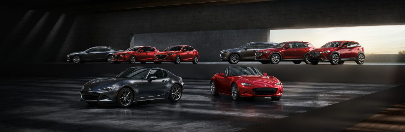 A variety of Mazda models are arrayed in some kind of garage. It is theoretically possible that they are certified pre-owned.