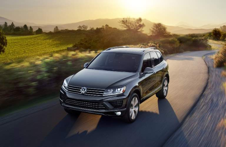 Black Volkswagen Touareg drives up a winding, misty country road.