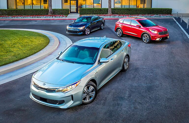 the 2017 Kia Optima Hybrid in the forefront with two other Kia vehicles behind