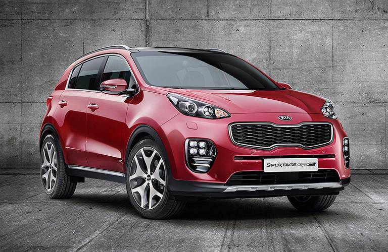 Red 2017 Kia Sportage in confident pose against a concrete wall