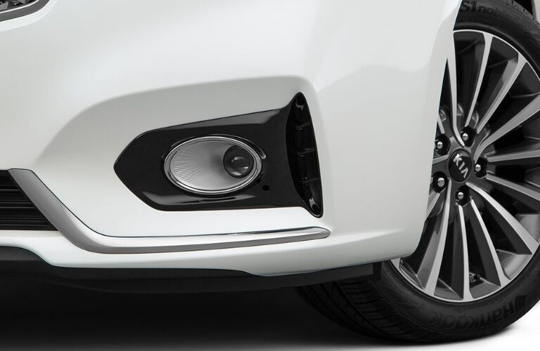 Exterior closeup view of the front bumper and front driver's side wheel of a white 2019 Kia Cadenza