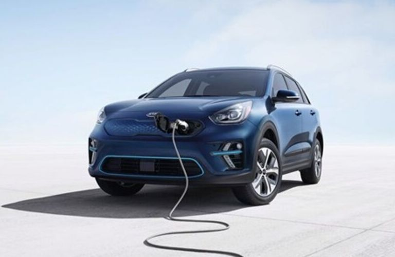 Exterior view of the front of a blue 2020 Kia Niro EV with the charging cord attached