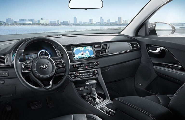 Interior view of the steering wheel, touchscreen, and front seating area inside a 2019 Kia Niro