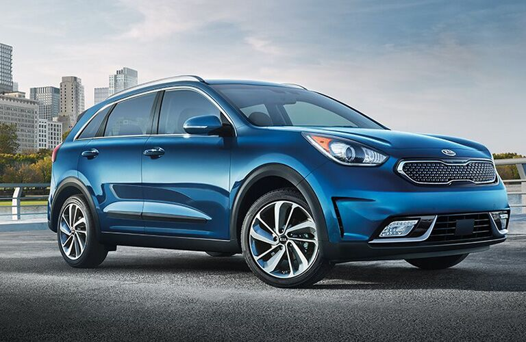 Exterior view of the front of a blue 2019 Kia Niro parked near the river in the city