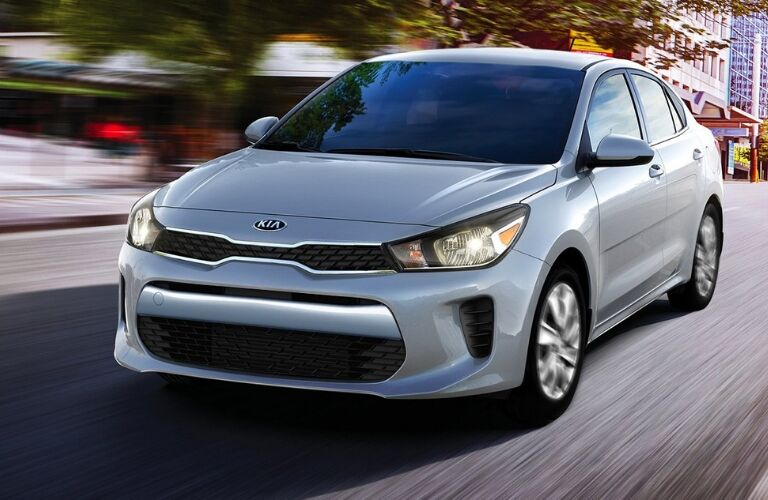 Exterior view of the front of a silver 2019 Kia Rio driving down a city street