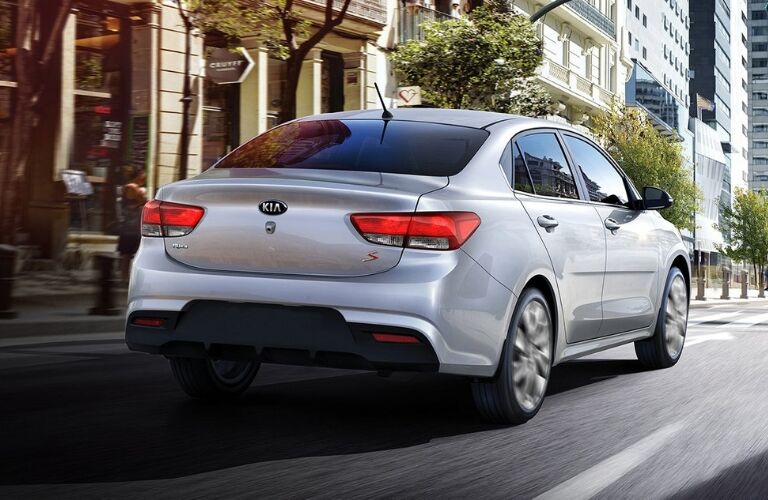 Exterior view of the rear of a silver 2019 Kia Rio driving down a city street