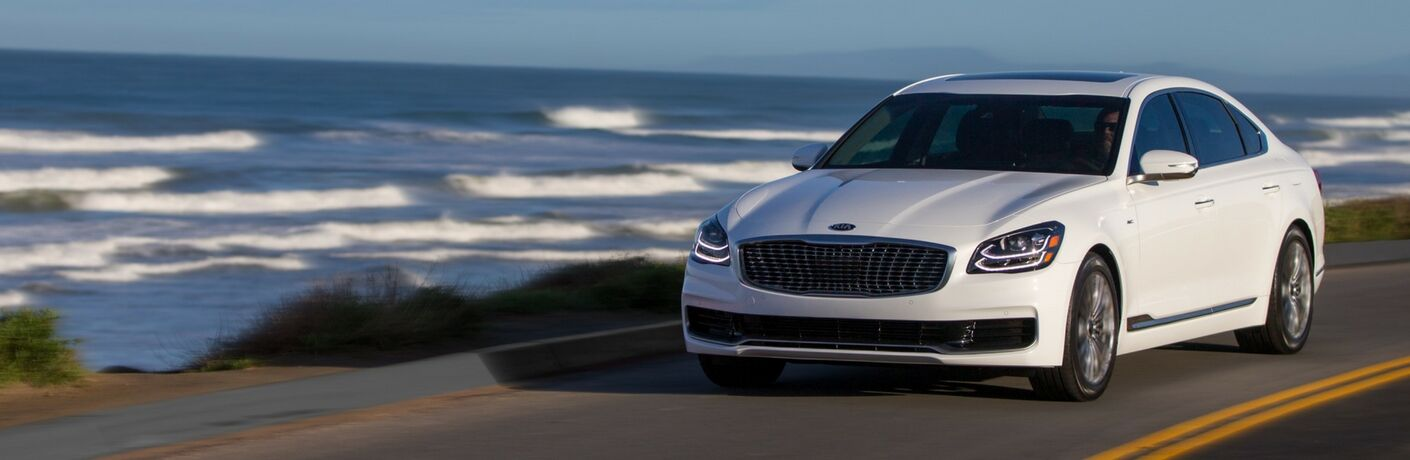 Exterior view of a white 2019 Kia K900 driving down a coastal road