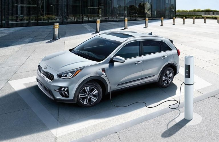 Exterior view of a silver 2020 Kia Niro Plug-In Hybrid plugged into an electric charger