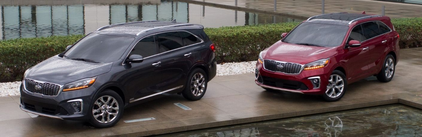 Exterior view of a gray and a red 2020 Kia Sorento parked near two reflection pools