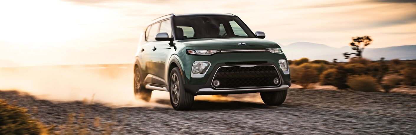 Exterior view of the front of a green 2020 Kia Soul driving down a dirt road in the desert