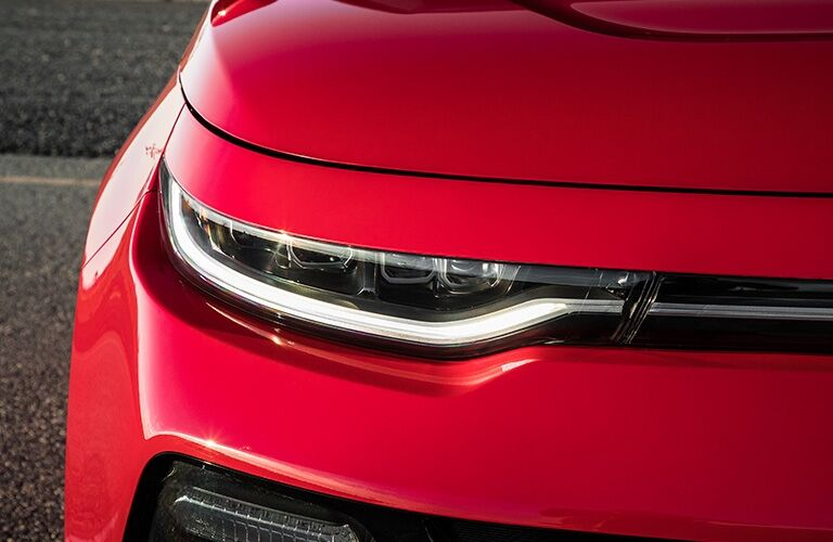 Exterior closeup view of the headlight and hood on a red 2020 Kia Soul