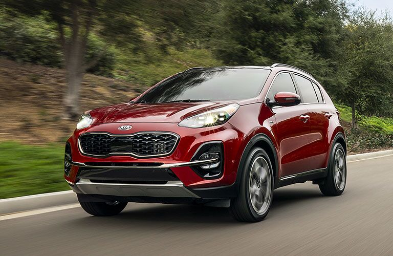 Exterior view of the front of a red 2020 Kia Sportage driving down a country road