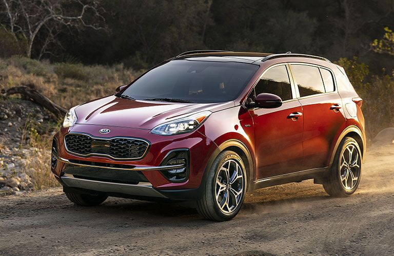 Exterior view of the front of a red 2020 Kia Sportage driving down a dirt road
