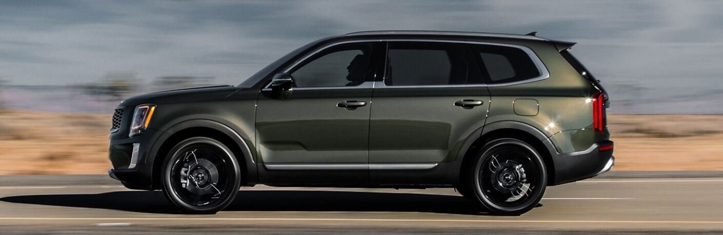 Exterior view of a green 2020 Kia Telluride driving down a desert highway
