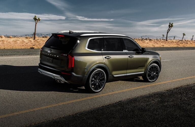 Exterior view of the rear of a green 2020 Kia Telluride driving down a desert highway