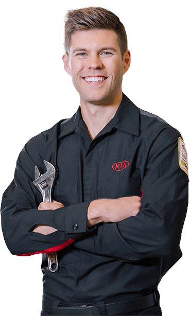 Smiling mechanic with arms crossed holds a wrench.