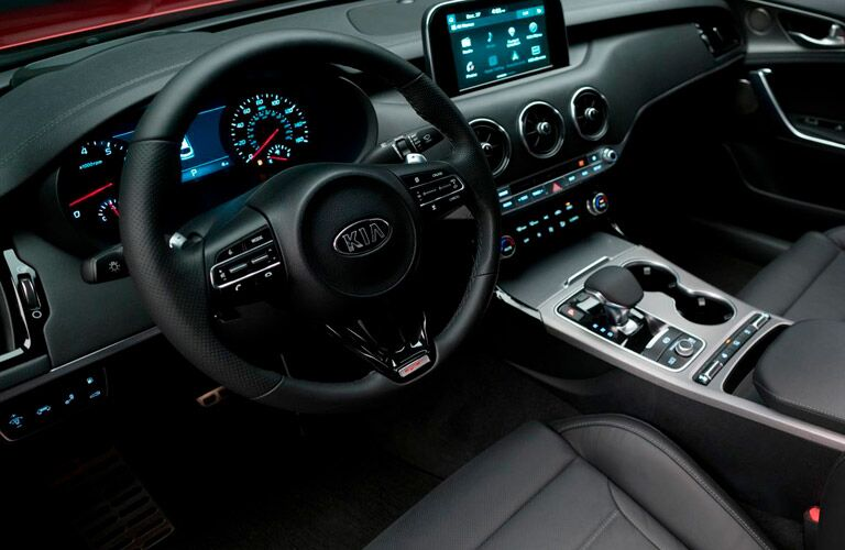 front interior of 2018 kia stinger including steering wheel, center console and infotainment system
