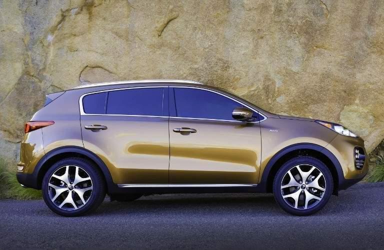 Profile view of gold 2018 Kia Sportage parked next to stone cliff