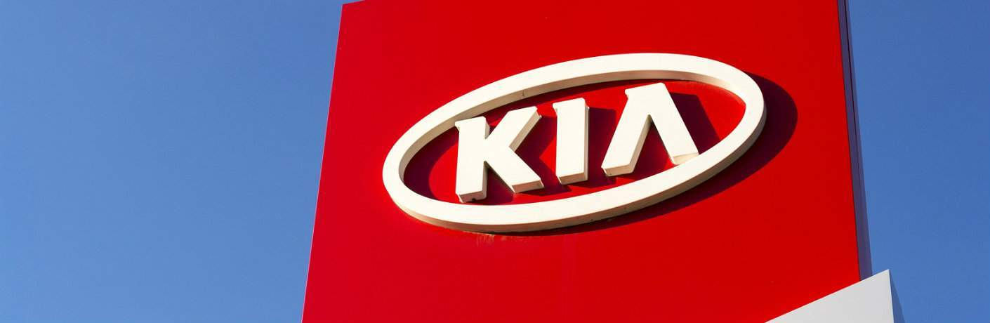 Exterior shot of Kia dealership facade with sky in background