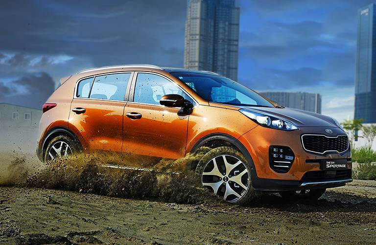 2017 Kia Sportage orange side view in sand